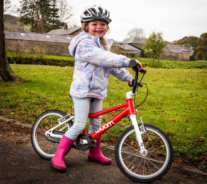 A little girl stands (smiling) astride a woom brand bike